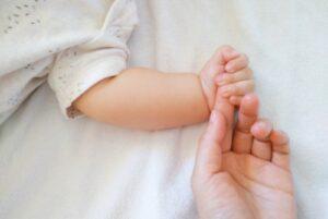 赤ちゃんがママの手を握りしめている