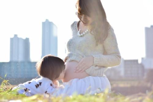 妊婦とその子供が仲睦まじく触れ合う様子
