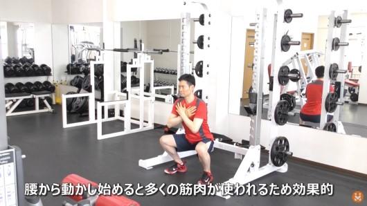 トレーニングジムで自分の体重で行うスクワットのエクササイズをしている男性