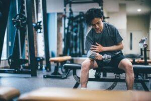 スポーツジムでダンベルで二の腕をトレーニングしている男性